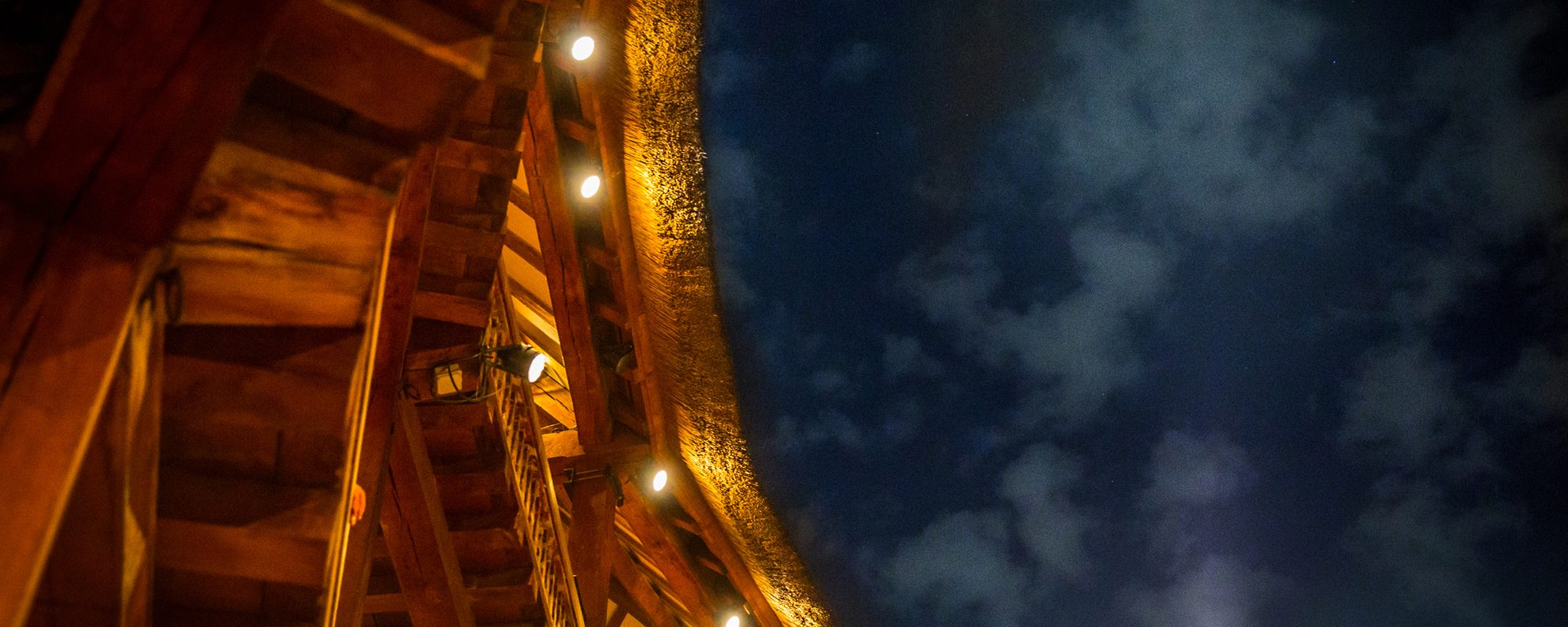 A close up of the corner of a roof of an open-air theatre, that shows an open sky and wooden beams