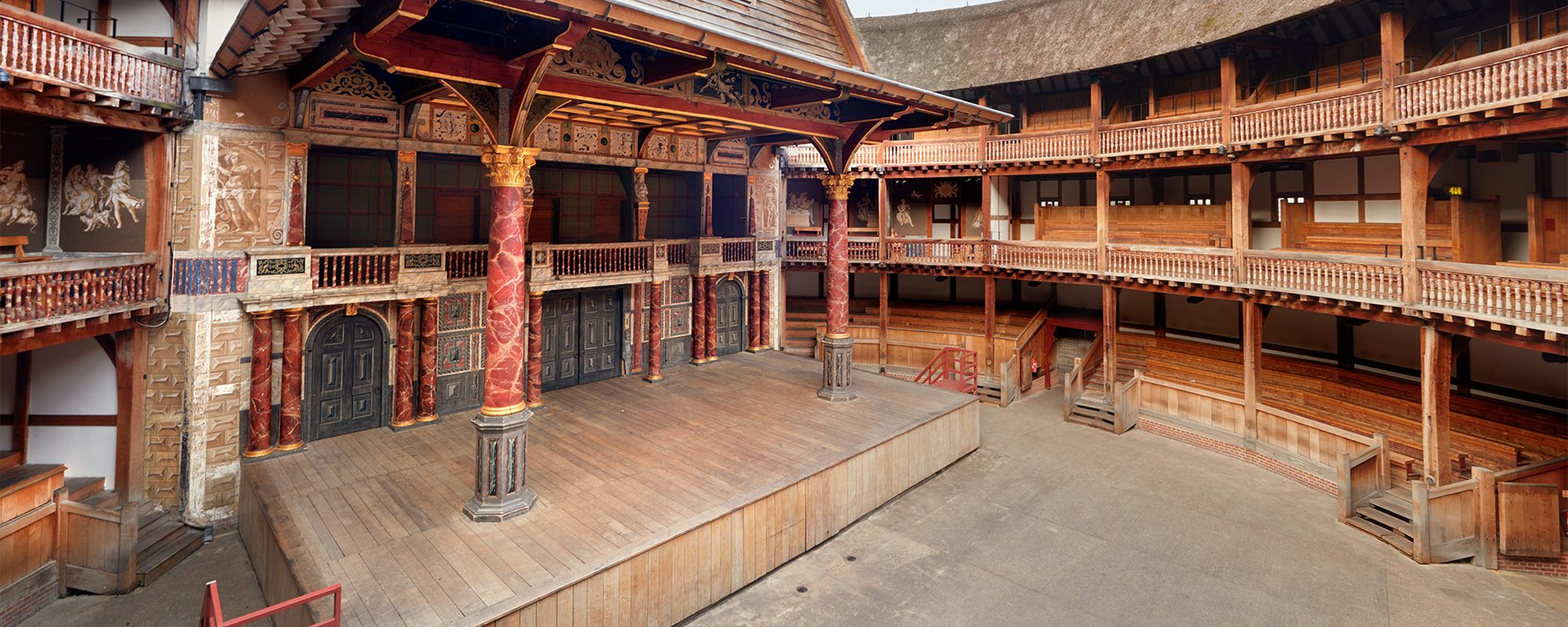 A view of an empty Globe Theatre, the image pans across the stage and seating bays.