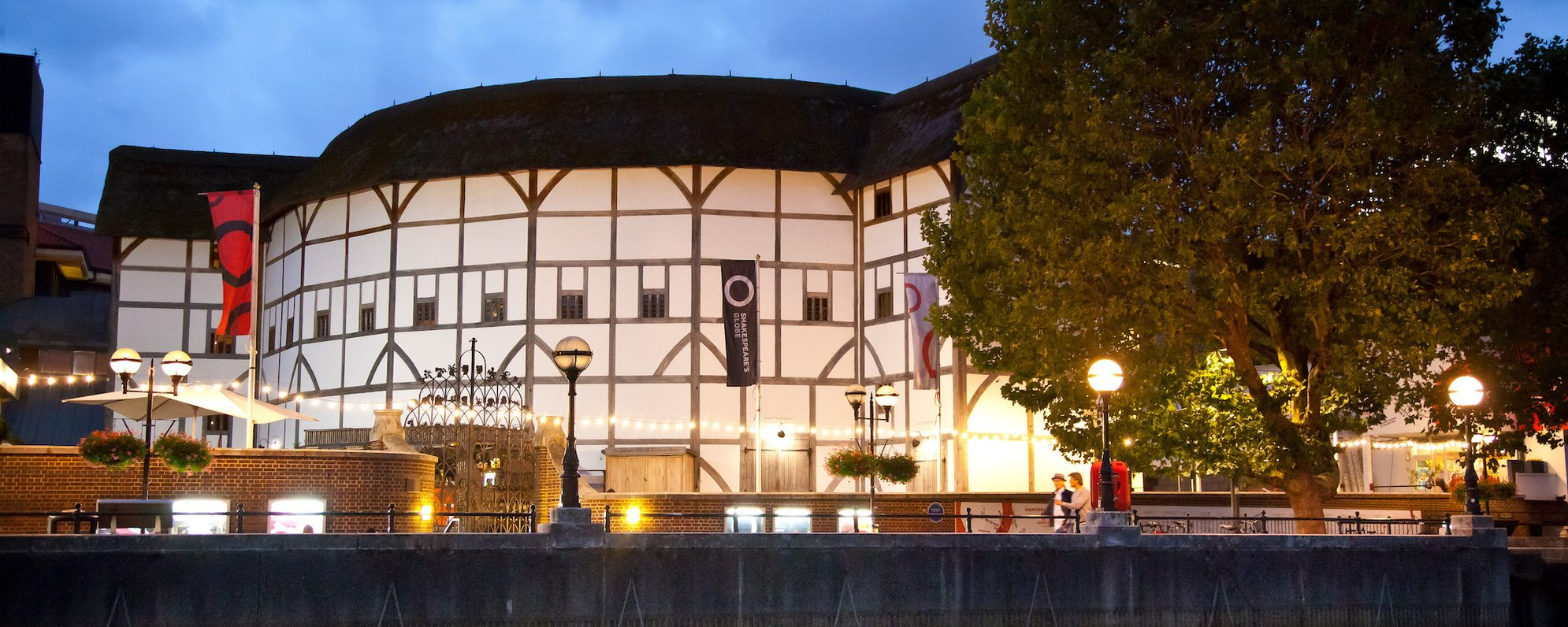 A thatched theatre at night illuminated by string lights