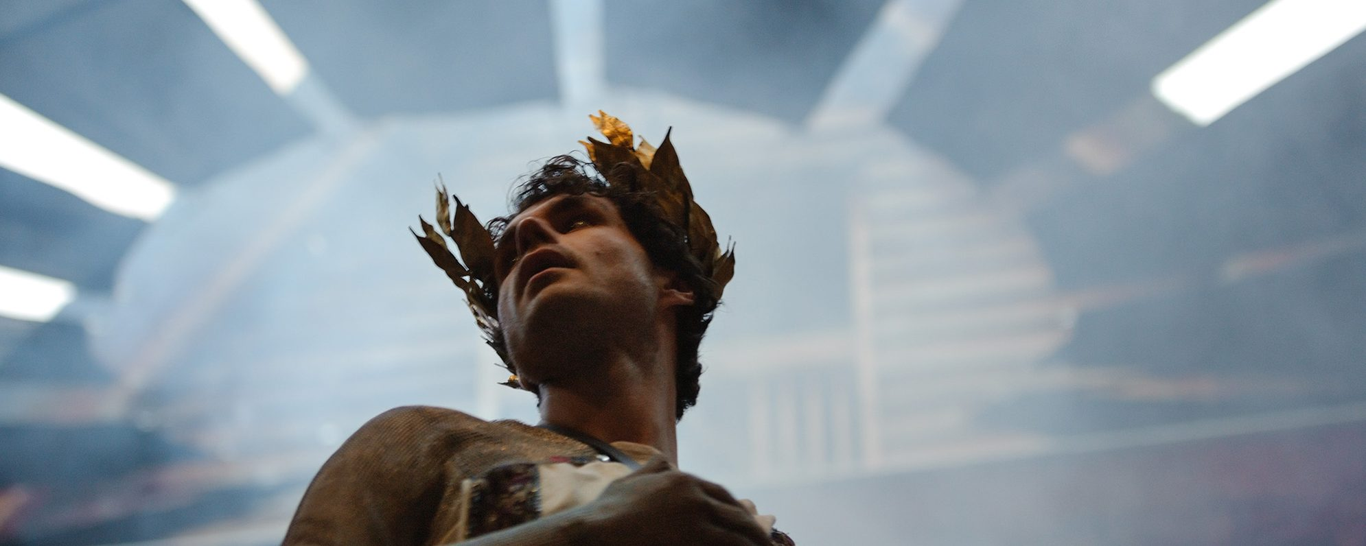 An actor wears a laurel (crown) made of gold leaves and looks up to the left, with a blue haze behind him