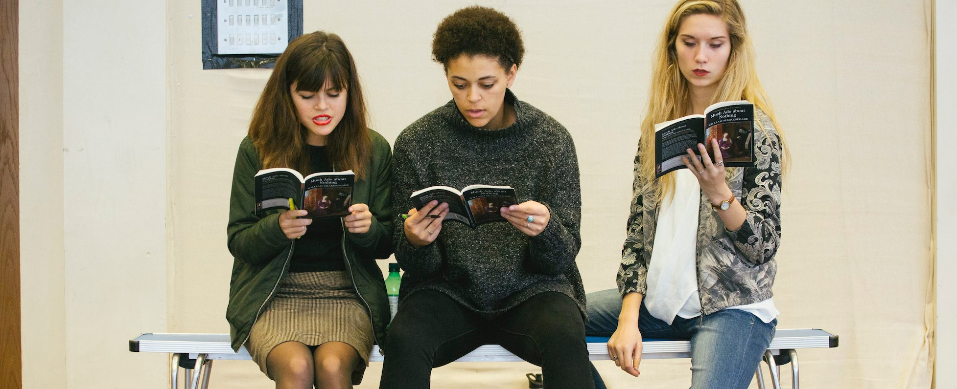 Three students sit on a bench reading a book