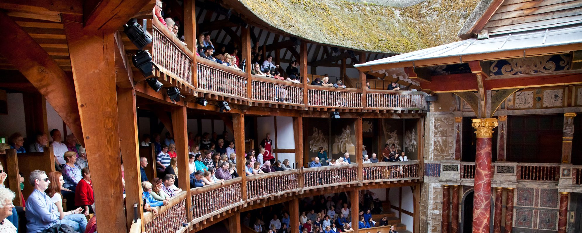 Audience members sit on an outdoor balcony watching a play in the Globe Theatre