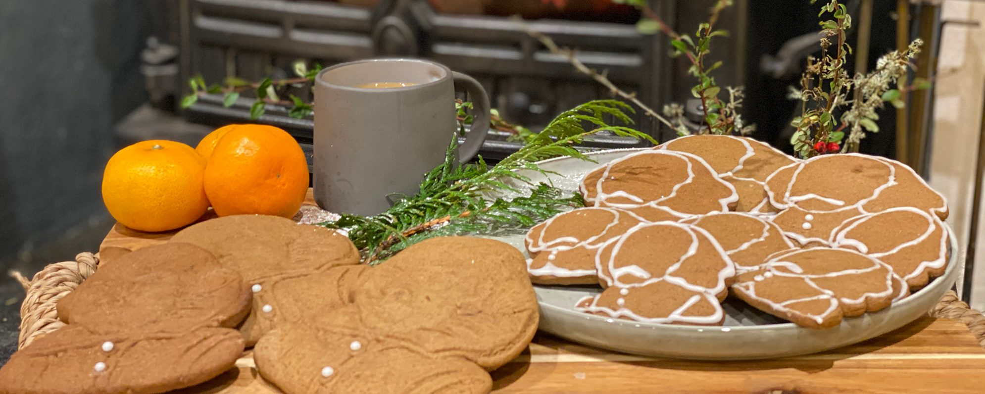 A table is laden with gingerbread biscuits in front of a log burning fire.