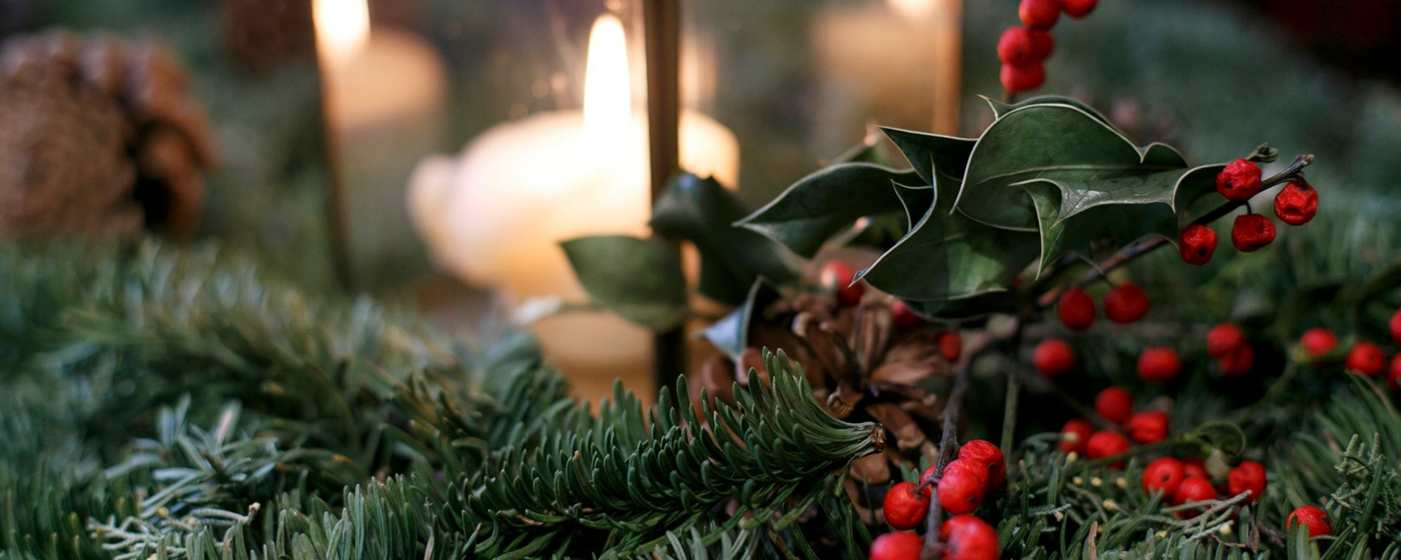 A close up of green holly, red berries and a lit candle.