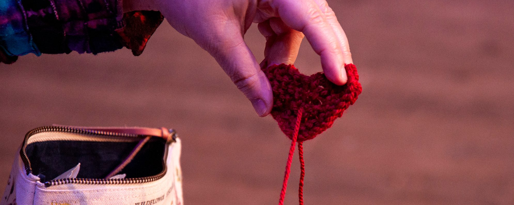 A small knitted heart, made with red yarn, is held up.