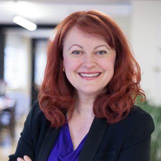 A sustainability advisor with red hair and blue top with black jacket