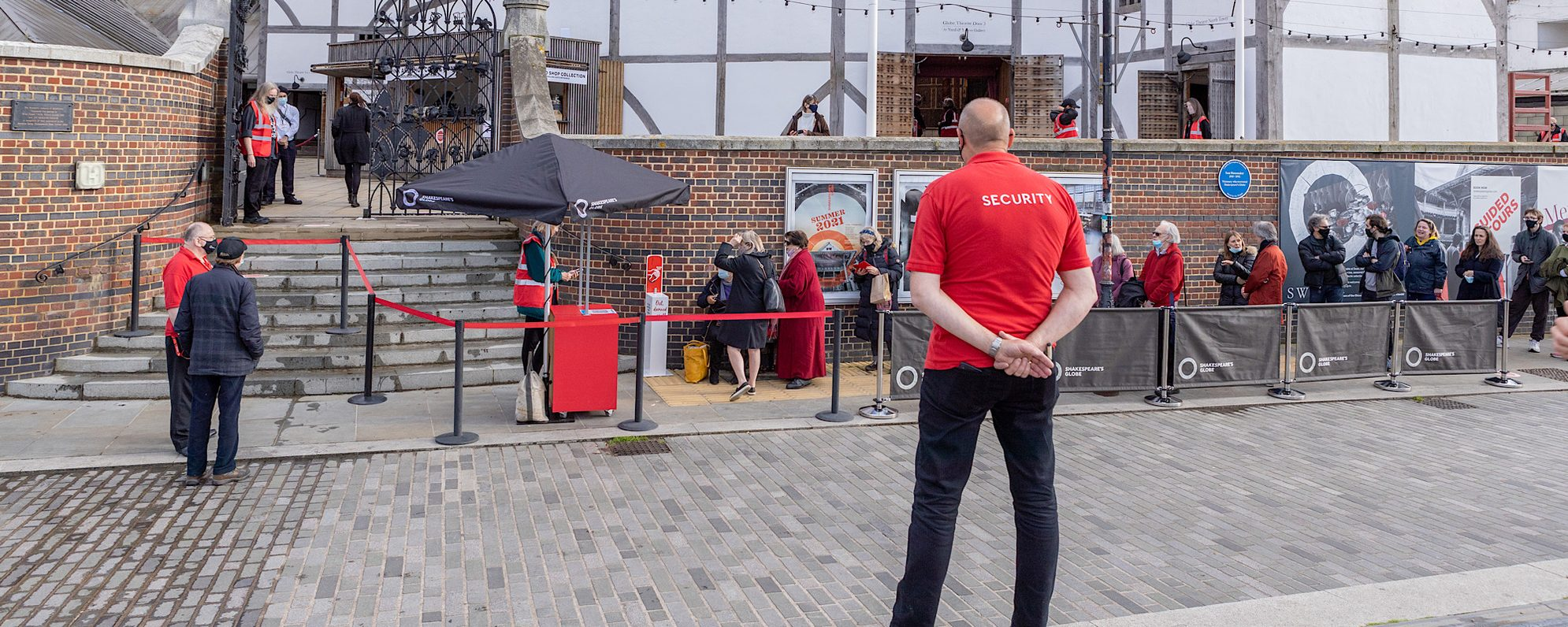 A person with a red shirt that has the words 'security' written on the back of it stands in front of an outdoor white theatre