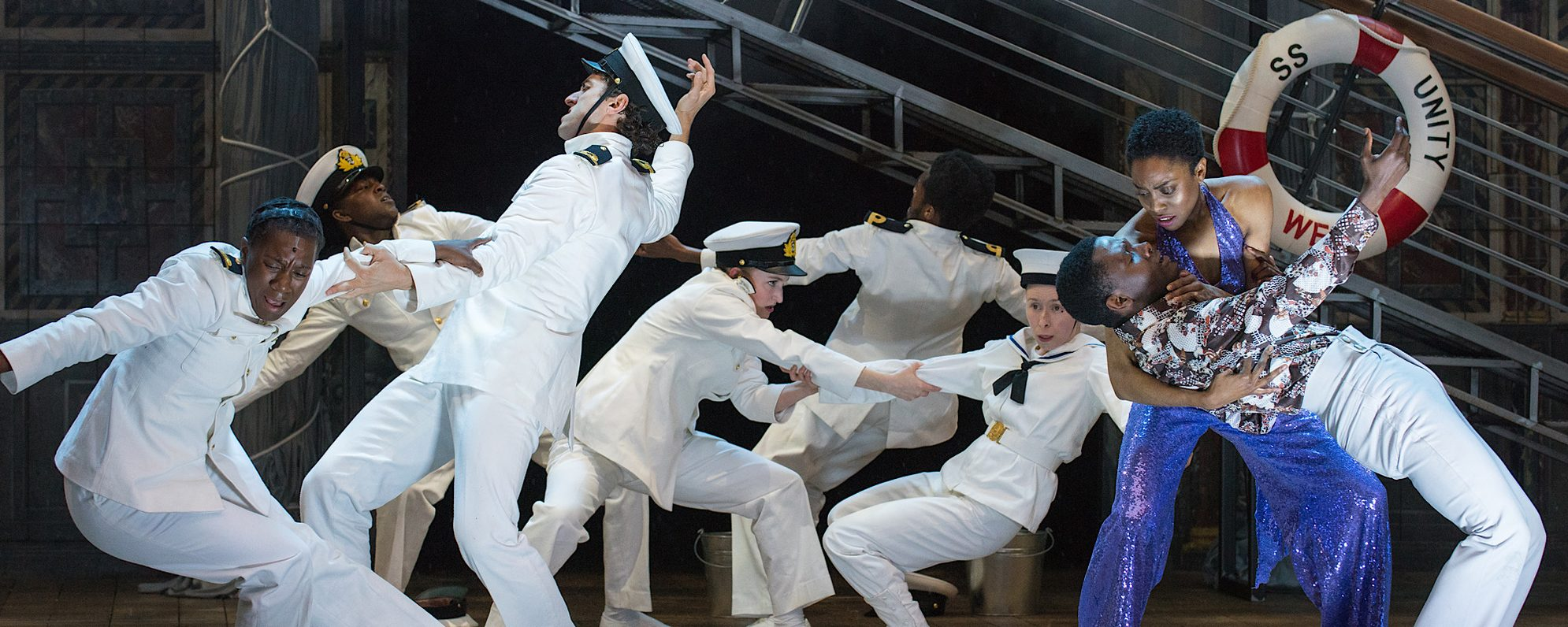 Actors dressed as sailors move in the background whilst two actors in the foreground embrace one another with sad looks on their faces