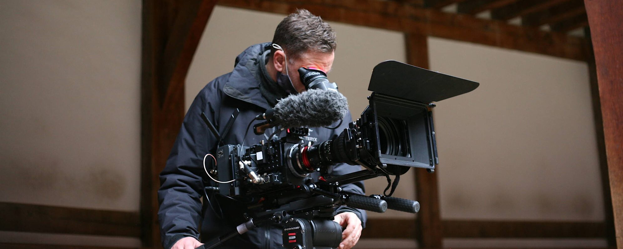 A cameraman in a black coat leans over a camera to look at what he is filming