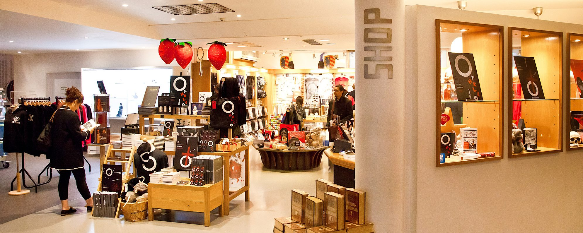A shop inside a theatre is brightly lit and decorated with lots of merchandise, the word 'shop' can be seen written vertically up the wall